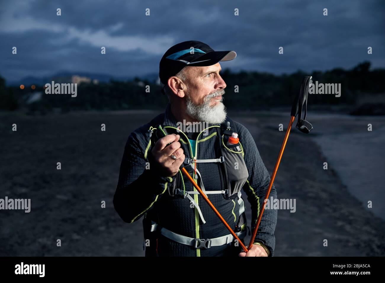 Portrait de l'athlète âgée homme à barbe grise et de bâtons de marche au fond de ciel nuageux sombre Banque D'Images