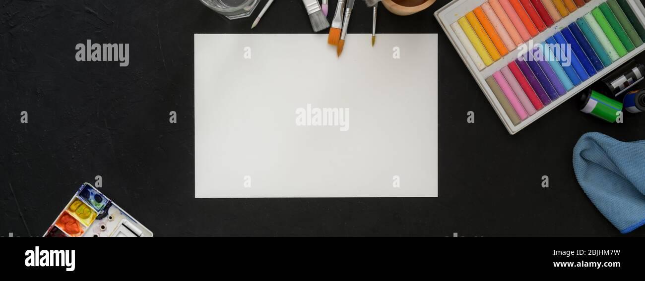 Vue de dessus de l'espace de travail des artistes avec papier d'esquisse, pastels à l'huile et outils de peinture sur la table noire Banque D'Images