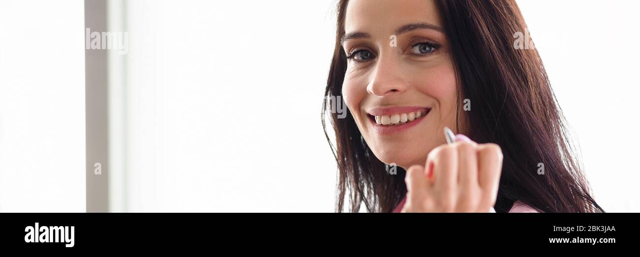 Une fille de travailleur de bureau tenant le visage du stylo et souriant Banque D'Images