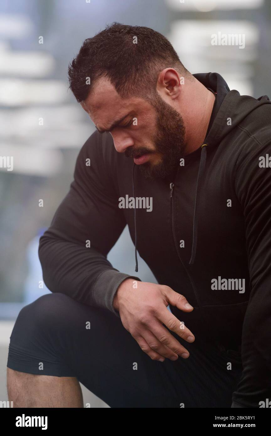 motivation sportive concept de jeune homme barbu fort athlète dans les vêtements de sport sweat à capuche penchant sur le genou pendant la pause dans l'entraînement Banque D'Images
