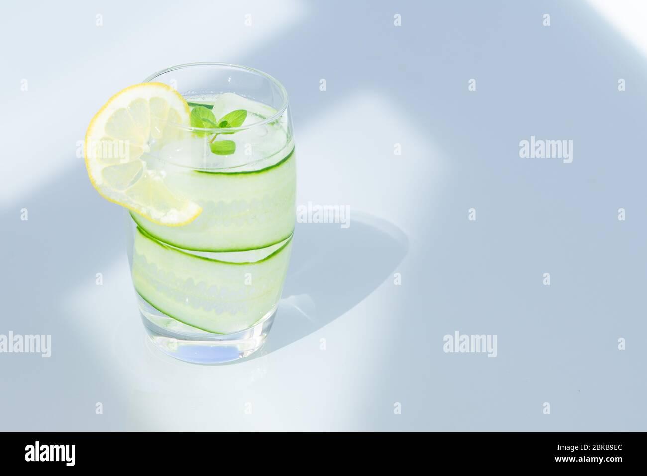 Verre d'eau avec citron, glace et concombre isolés. Espace de copie. Banque D'Images