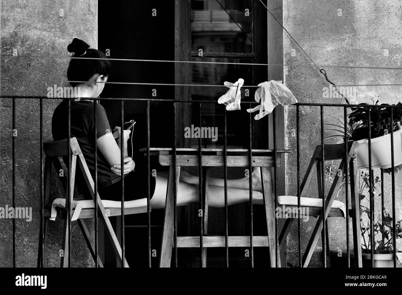 Une jeune femme s'est assise sur son balcon à l'aide de son smartphone. Banque D'Images