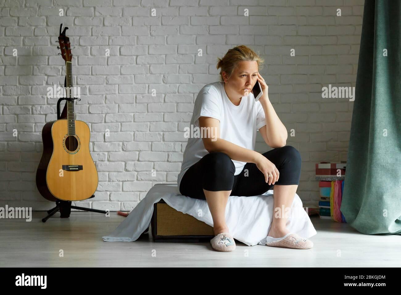 Triste femme parlant au téléphone dans le salon assis dans l'autocar. 40 ans femme portant des vêtements de maison. Banque D'Images