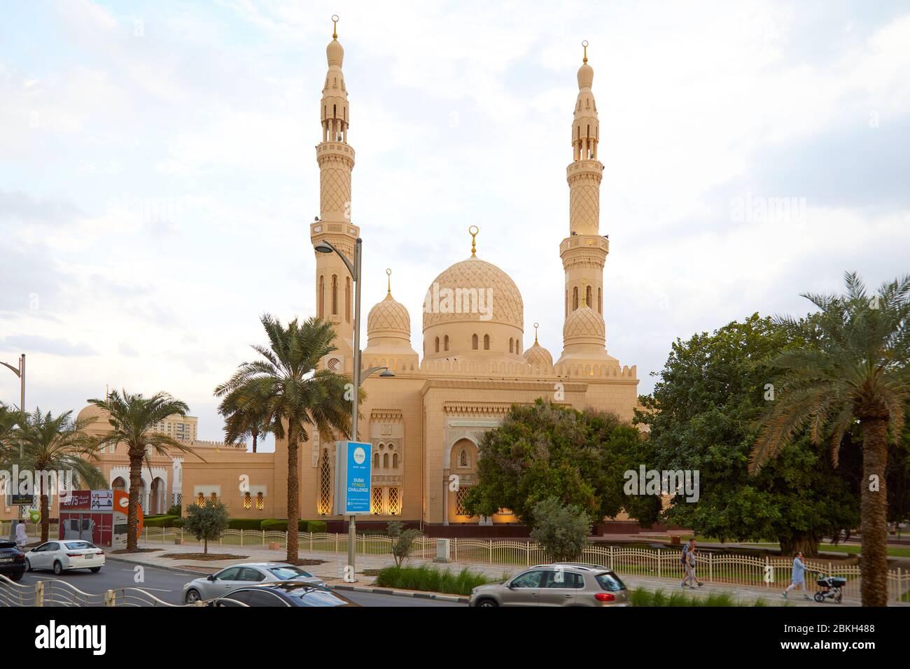 DUBAÏ, EMIRATS ARABES UNIS - 21 NOVEMBRE 2019 : vue sur la mosquée de Jumeirah avec palmiers et personnes passant dans l'après-midi Banque D'Images