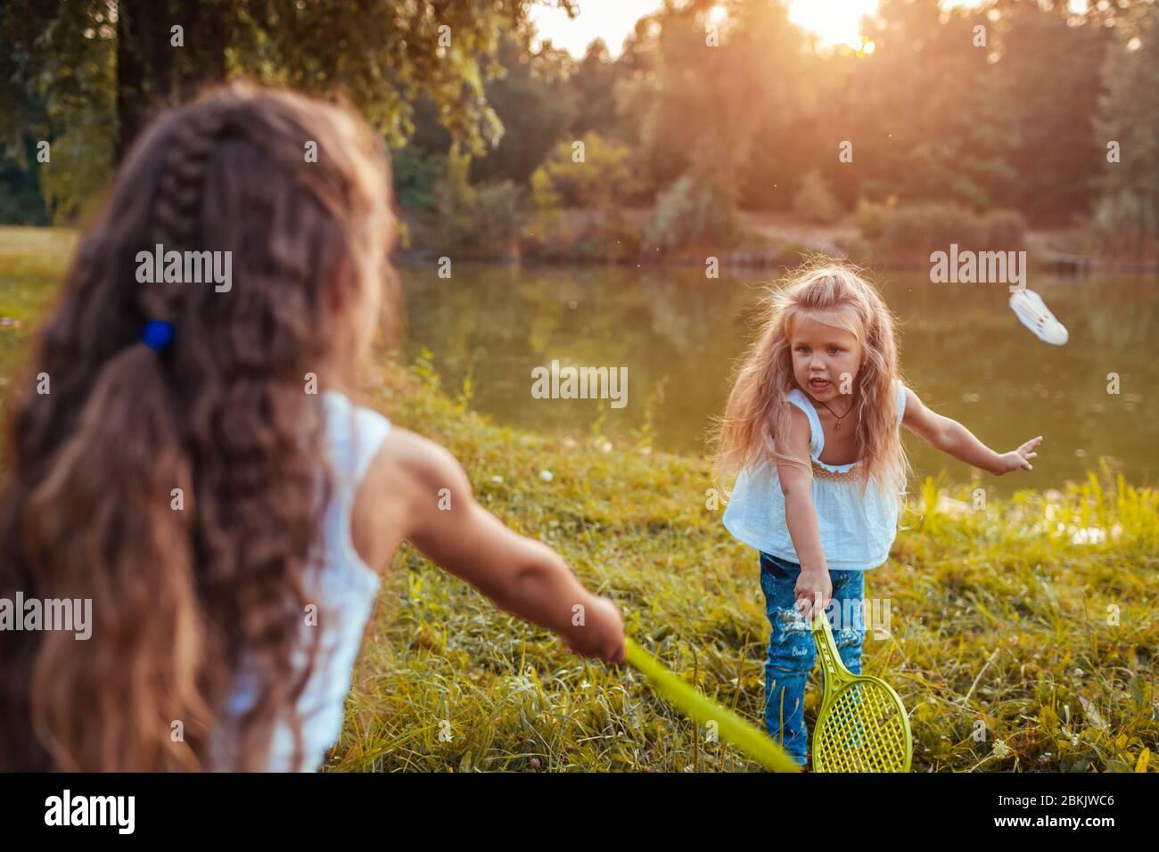 Badminton. Petite fille jouant au badminton avec sœur dans le parc de printemps. Enfants s'amuser à l'extérieur. Jeux en plein air Banque D'Images