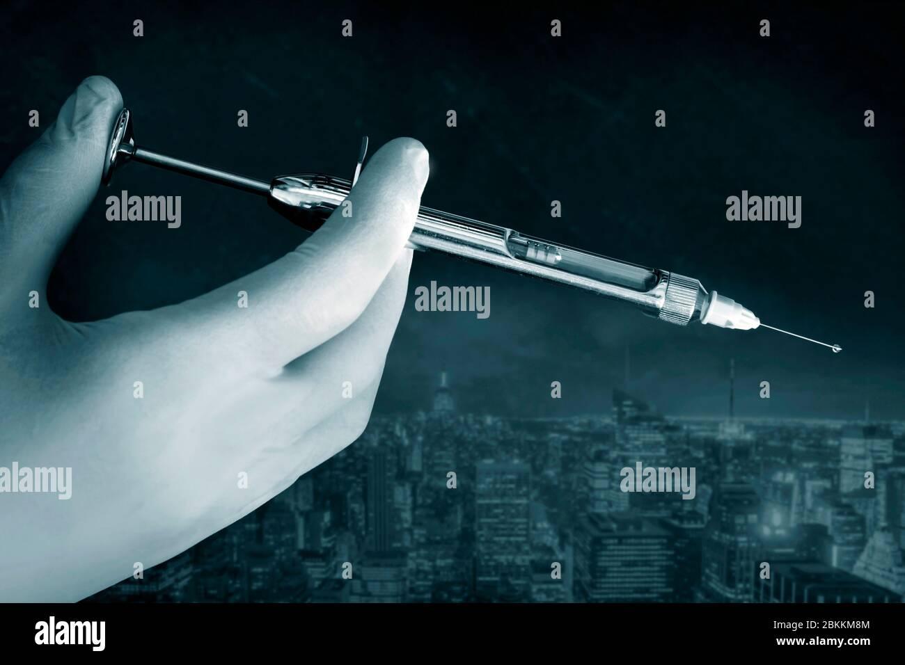 La main du médecin dans un gant blanc tient la seringue avec le jet de préparation de l'aiguille Banque D'Images