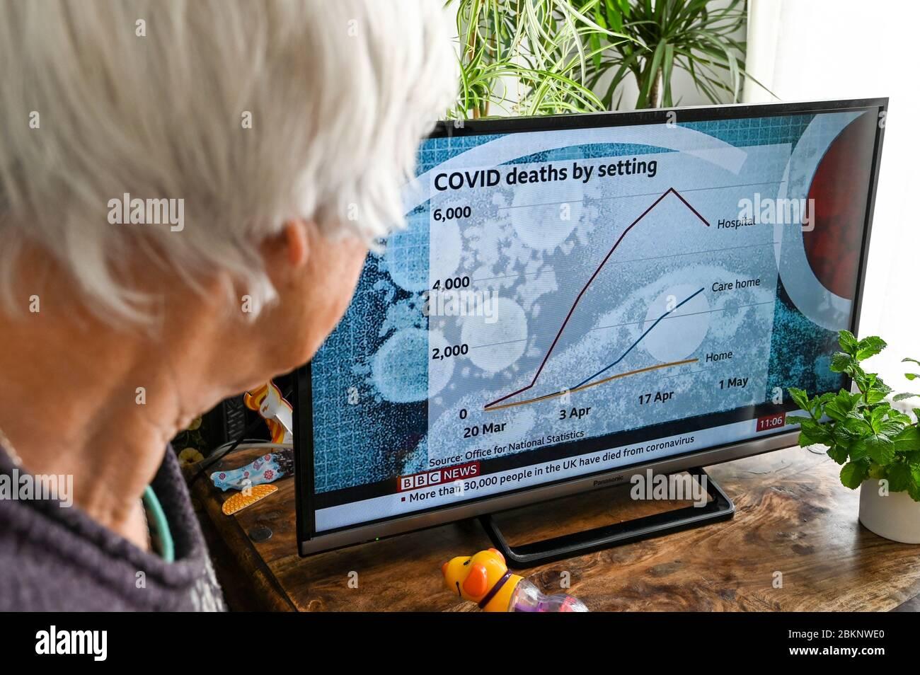 Une femme âgée regarde les nouvelles de la télévision avec un graphique montrant les décès au Royaume-Uni dans les hôpitaux, les maisons de soins et à la maison. Banque D'Images