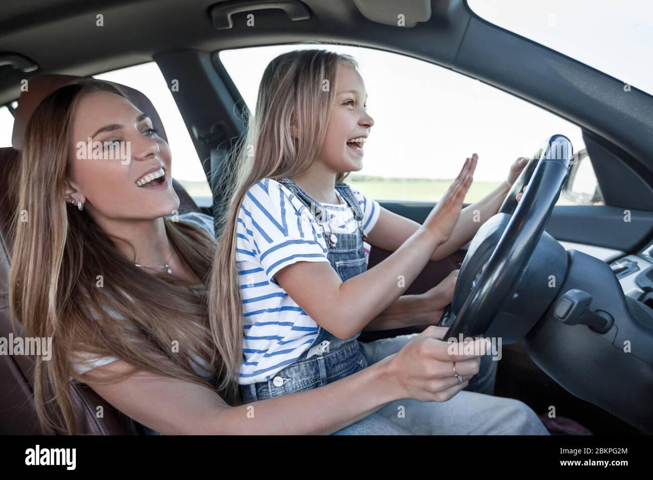 Maman enseigne à sa petite fille à conduire Banque D'Images