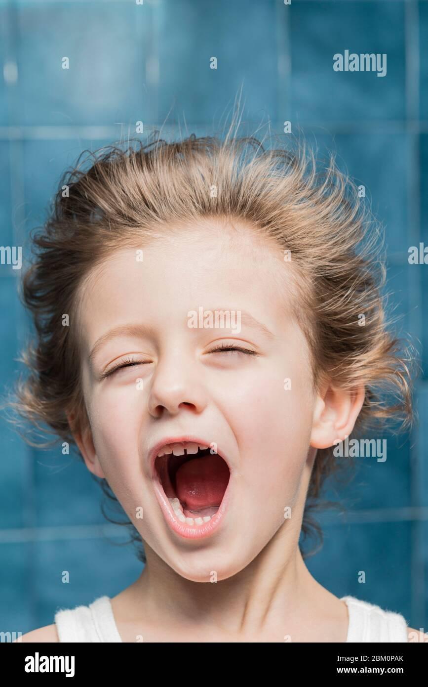 Un enfant dans la salle de bains sèche ses cheveux avec un sèche-cheveux, en faisant des gestes. Banque D'Images