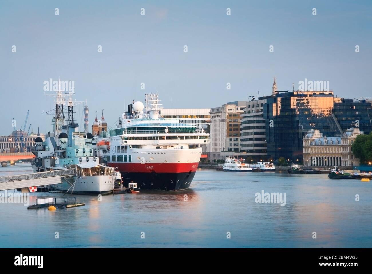 HMS Belfast et un bateau de croisière sur la Tamise à Londres. Banque D'Images