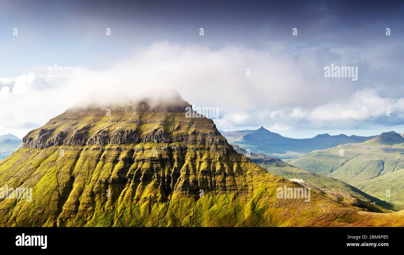 Foggy Mountain peaks et les nuages couvrant la mer et les montagnes. Panoramical view à partir de la célèbre place - Sornfelli sur Streymoy island, îles Féroé, Danemark. Photographie de paysage Banque D'Images