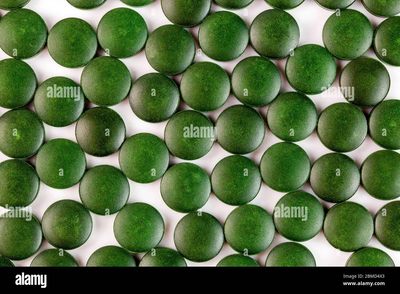 de nombreux comprimés verts de spiruline organique ont posé ramdomly dans une couche sur une surface plane et blanche Banque D'Images