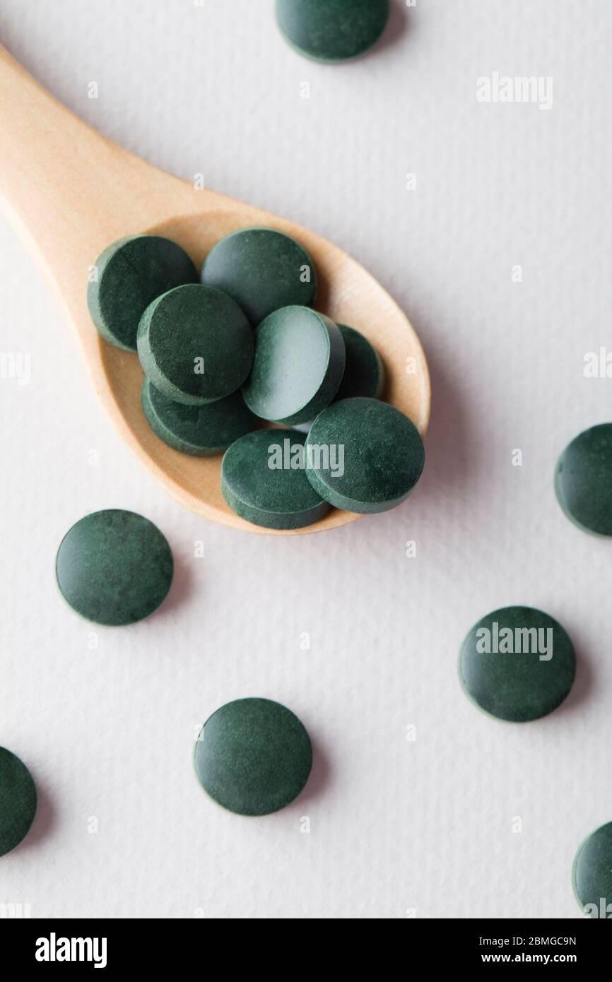 comprimés ronds verts de spiruline dans une cuillère en bois sur fond blanc gros plan vertical Banque D'Images