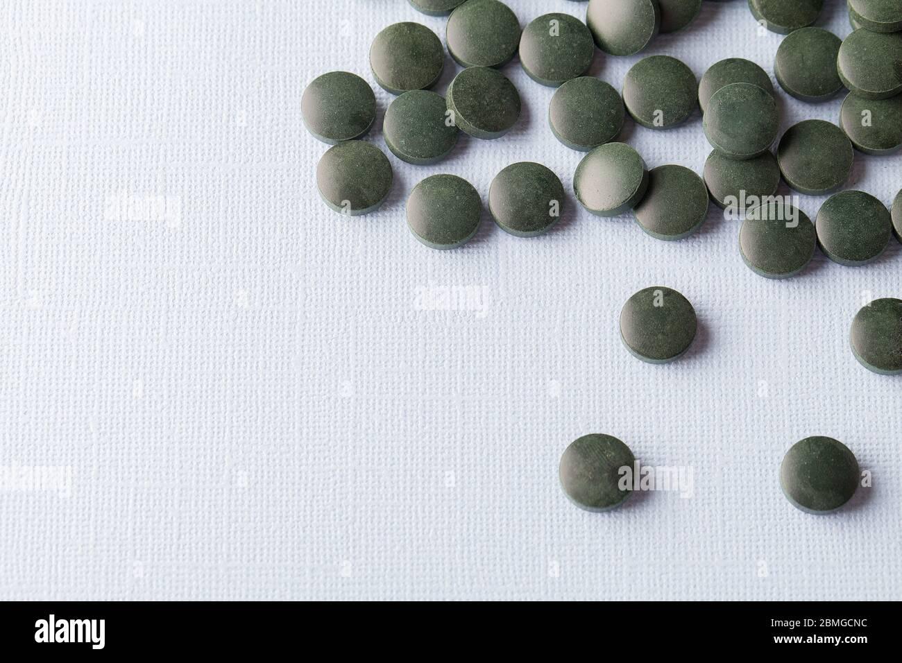 tablettes rondes vertes de spiruline sur fond blanc gros plan de l'espace de copie Banque D'Images