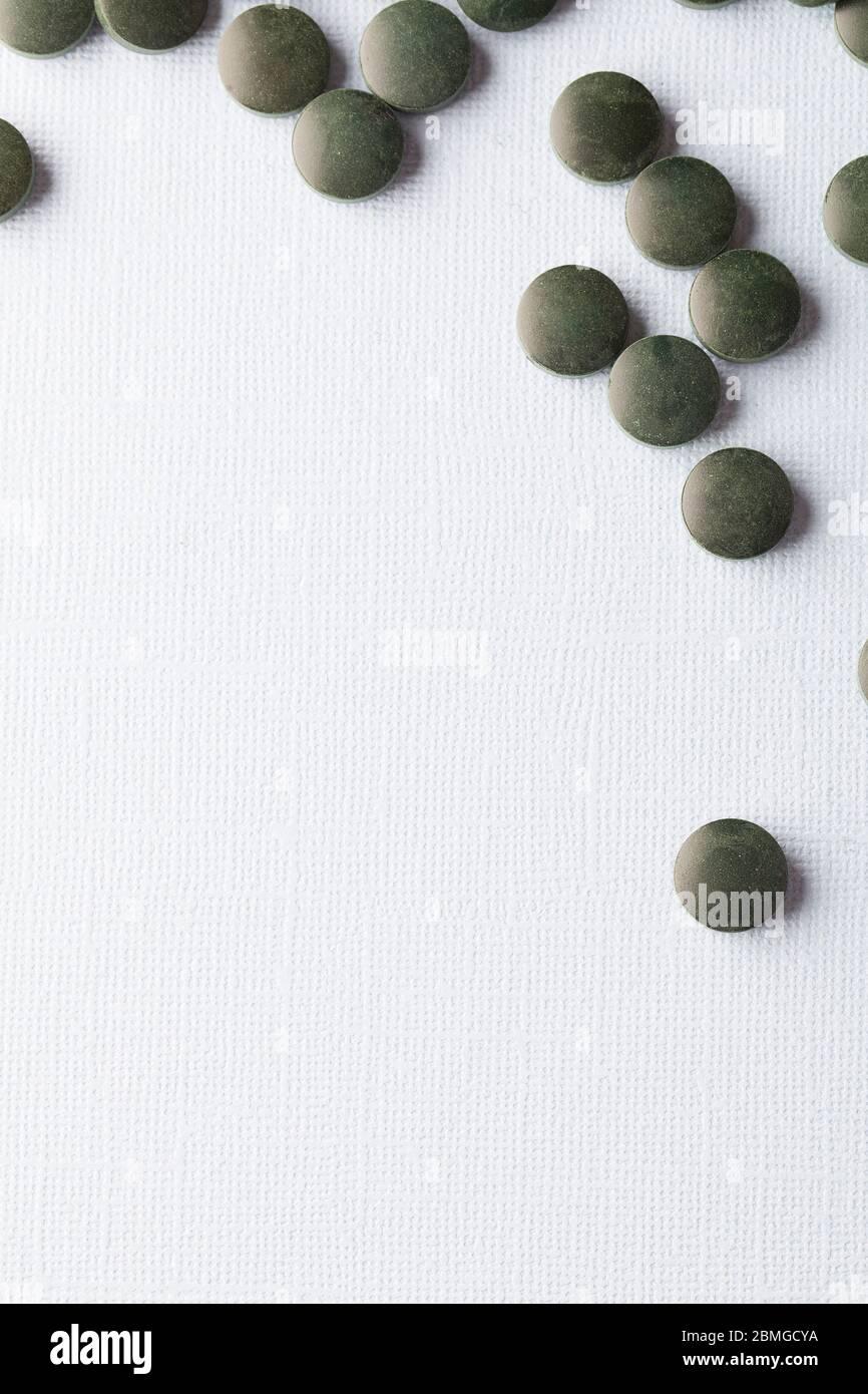 les comprimés ronds verts de spiruline sur fond blanc permettent de gros plan de l'espace de copie vertical Banque D'Images