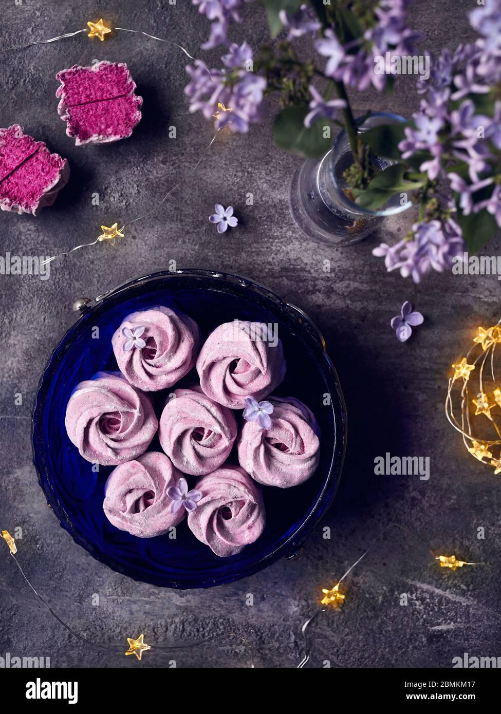 Bleu-violet doux maison Zephyr ou Marshmallow de cassis près des fleurs lilas et des étoiles magiques lumières sur fond sombre vue de dessus Banque D'Images