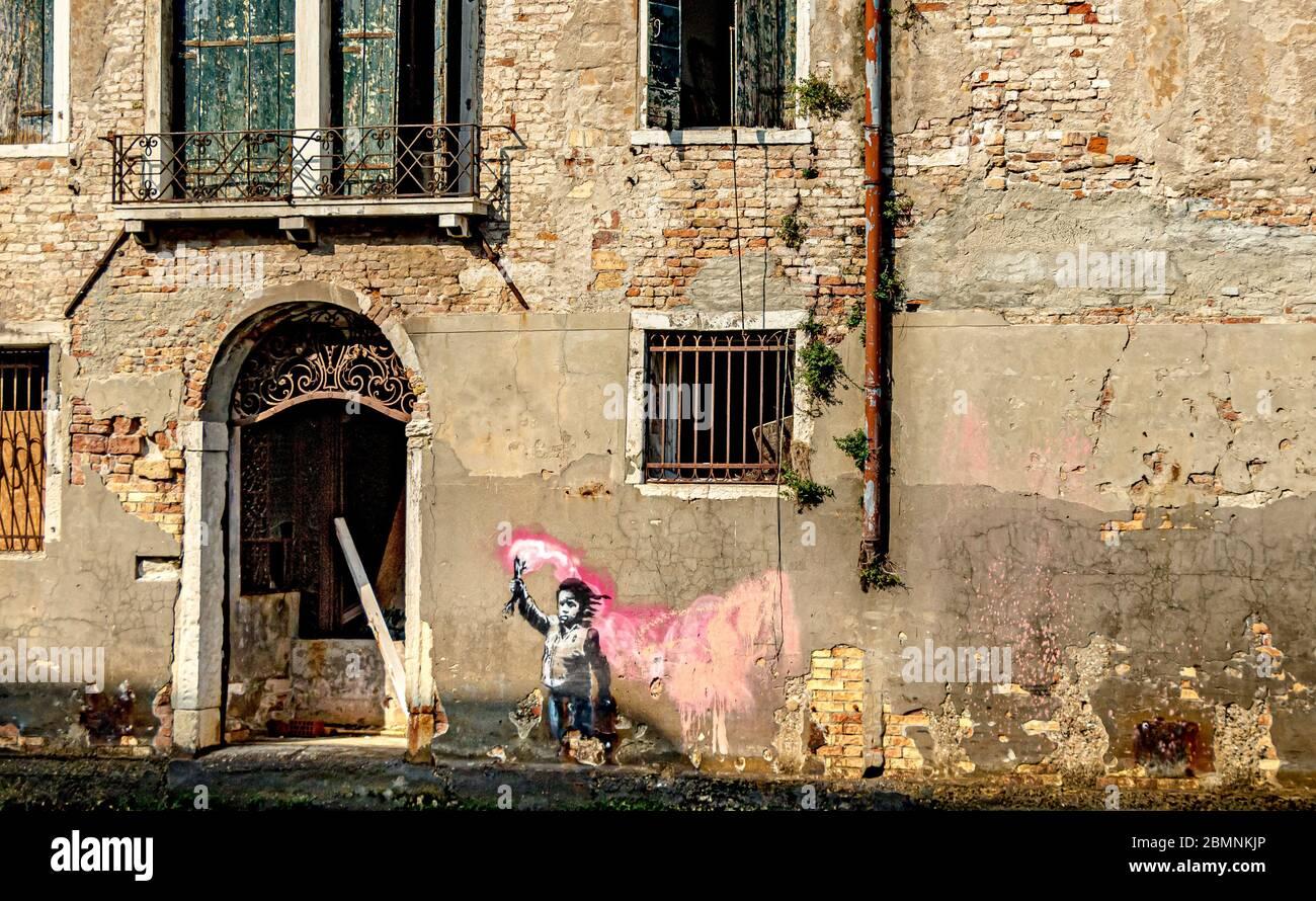Une peinture murale Banksy représentant un enfant migrant tenant une éruption rose, sur un bâtiment à côté d'un canal dans le quartier Dorsoduro de Venise, Italie Banque D'Images