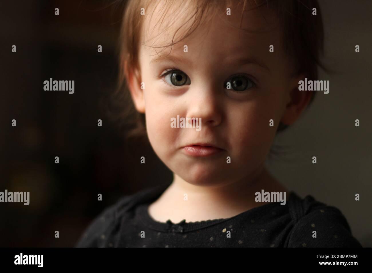 Portrait en gros plan d'un bébé blanc mignon avec un visage sale dans un environnement doux et flou Banque D'Images