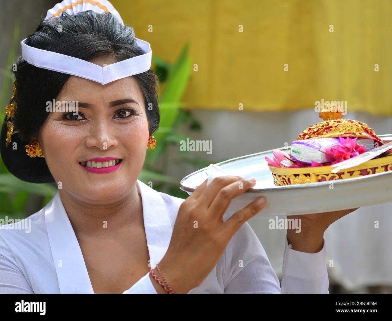 La femme indonésienne balinaise en blanc offre des offrandes lors d'une cérémonie religieuse de temple hindou et sourit pour la caméra. Banque D'Images