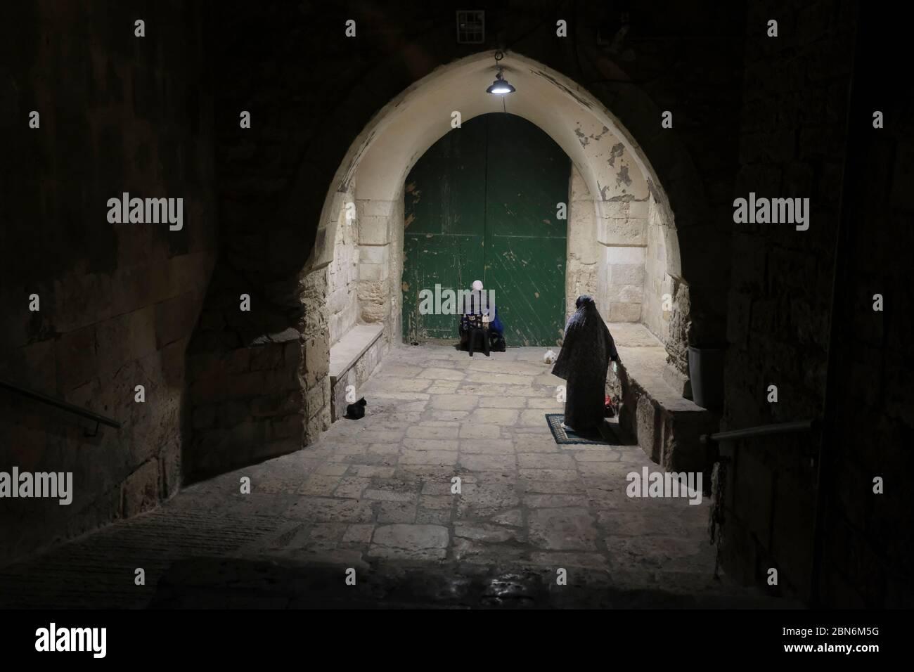 Jérusalem, ISRAËL, 12 mai 2020 : des femmes musulmanes palestiniennes adorantes accomplissant la prière de Taraweeh pendant le mois sacré musulman du Ramadan à l'extérieur de la mosquée fermée d'al-Aqsa dans la vieille ville de Jérusalem, dans le cadre de la pandémie COVID-19, le 12 mai 2020. La mosquée Al-Aqsa, située sur la place du Mont du Temple à Jérusalem, a été fermée il y a 51 jours par le Waqf, l'organisme religieux qui gère les lieux saints musulmans de la ville sainte, une mesure exceptionnelle visant à enrayer la pandémie du coronavirus. Crédit : Eddie Gerald / Alay Live News Banque D'Images