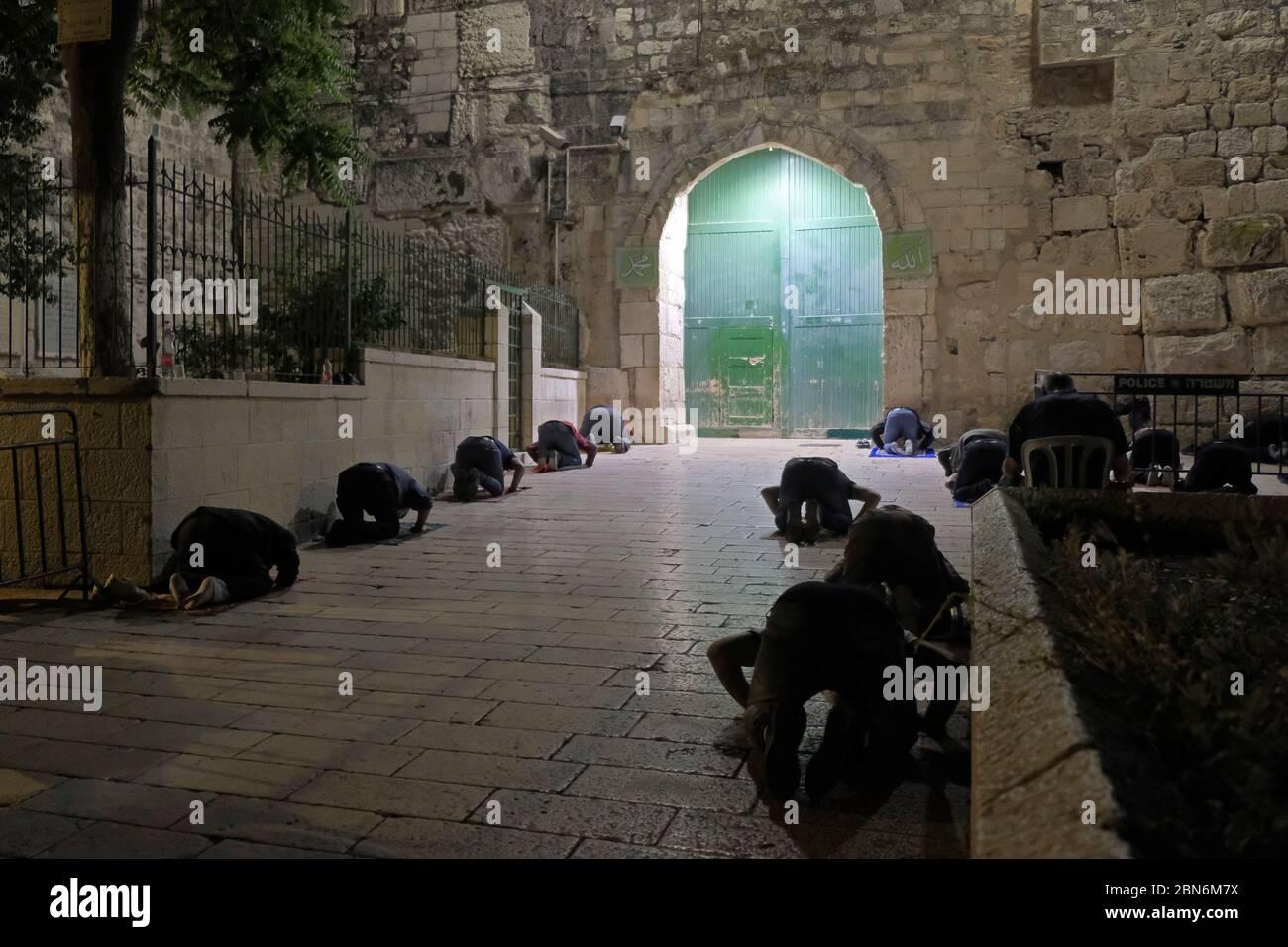 Jérusalem, ISRAËL, 12 mai 2020 : des fidèles musulmans palestiniens accomplissent la prière de Taraweeh pendant le mois sacré musulman du Ramadan, à l'extérieur de la mosquée fermée d'al-Aqsa dans la vieille ville de Jérusalem, dans le cadre de la pandémie COVID-19, le 12 mai 2020. La mosquée Al-Aqsa, située sur la place du Mont du Temple à Jérusalem, a été fermée il y a 51 jours par le Waqf, l'organisme religieux qui gère les lieux saints musulmans de la ville sainte, une mesure exceptionnelle visant à enrayer la pandémie du coronavirus. Crédit : Eddie Gerald / Alay Live News Banque D'Images