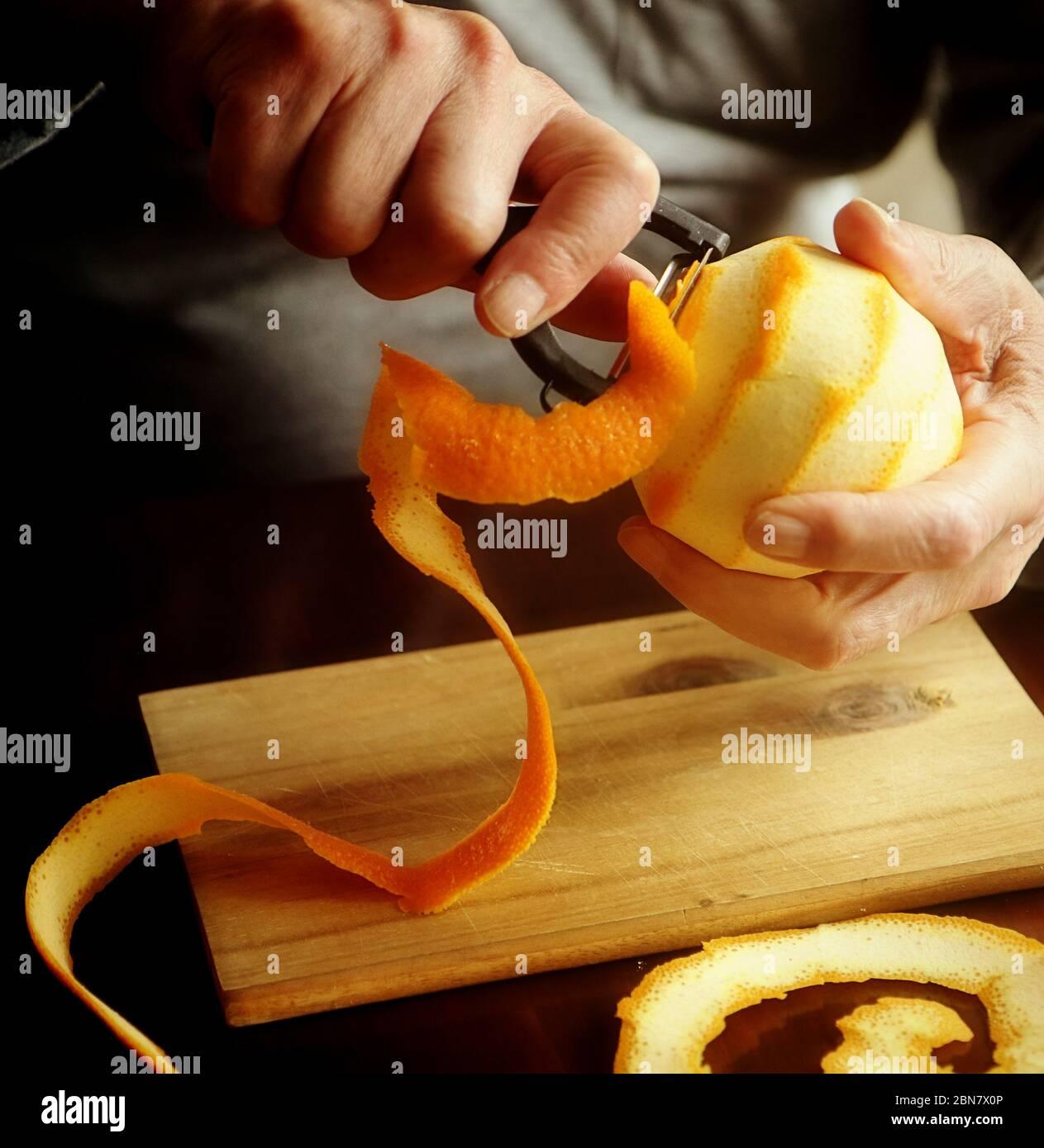Préparation de la marmelade d'orange : retirer le zeste d'orange avec un éplucheur de légumes pointu, à ajouter ensuite à la marmelade Banque D'Images