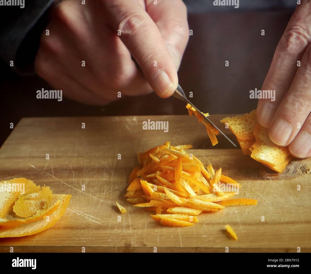 Préparation de la marmelade d'orange : couper avec un couteau tranchant le zeste d'orange en petites tranches pour les ajouter à la réserve maison Banque D'Images