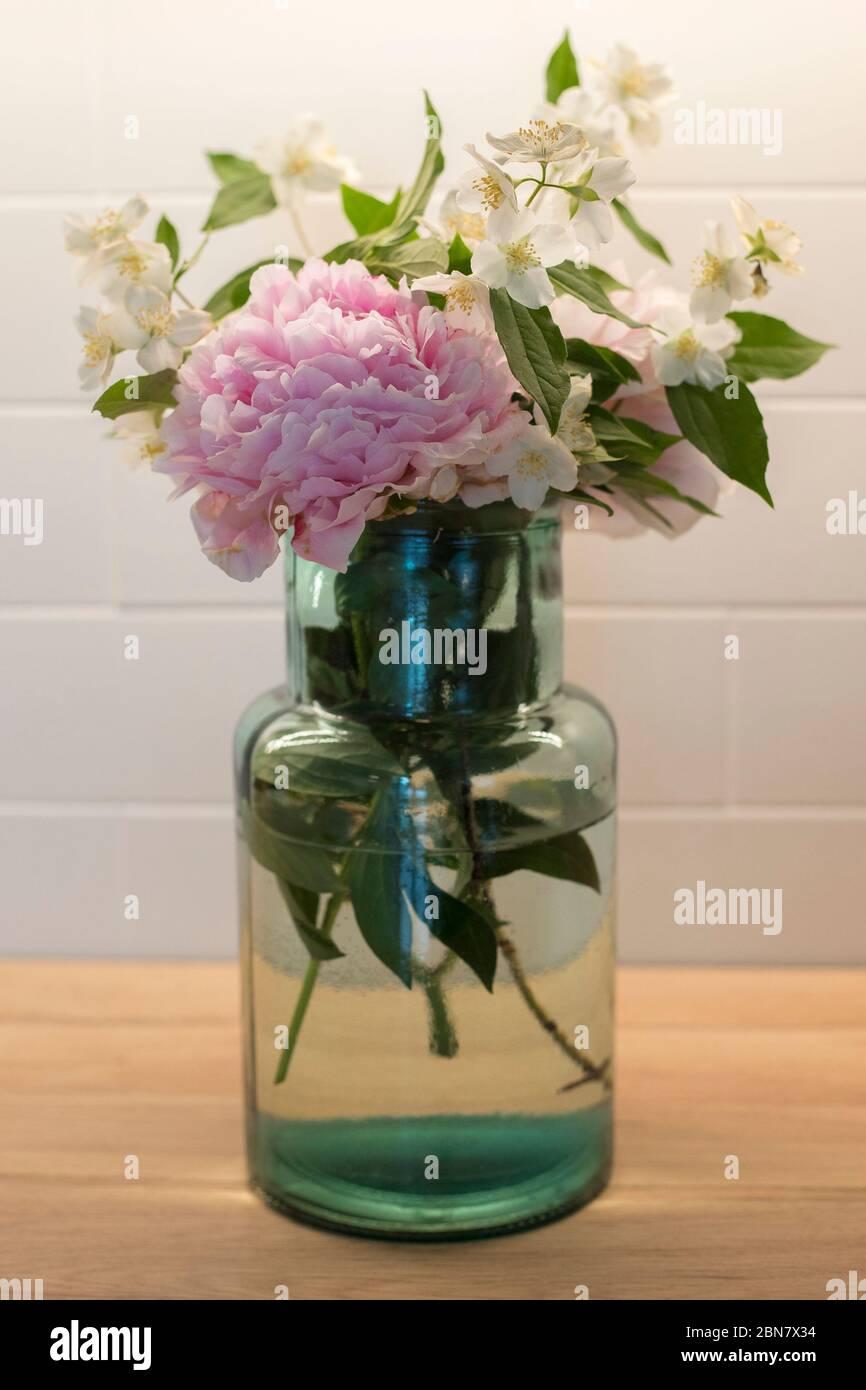 Bouquet de fleurs avec pivoine (paeonia) et orange (philadelphus), dans un vase en verre bleu. Tir vertical. Banque D'Images