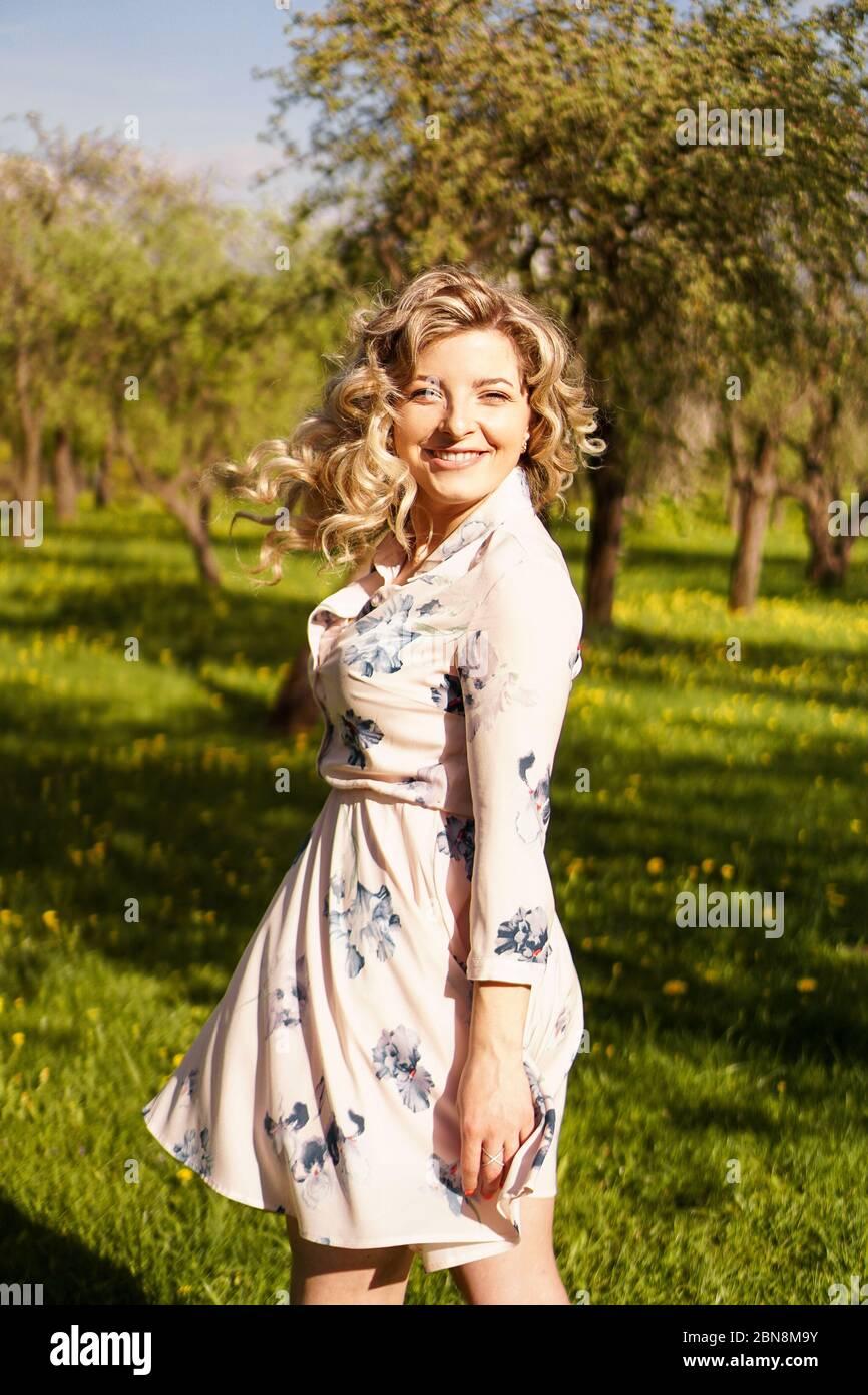 Bonne jeune femme aux cheveux blonds, portant une robe, posant à l'extérieur dans un jardin avec des cerisiers au soleil, souriant. Boucles qui flottent dans le vent Banque D'Images