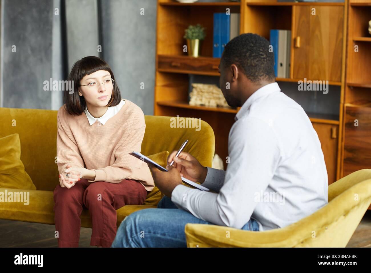 Jeune femme assise sur un canapé et parlant à un homme africain pendant qu'il prend des notes dans un document au bureau Banque D'Images