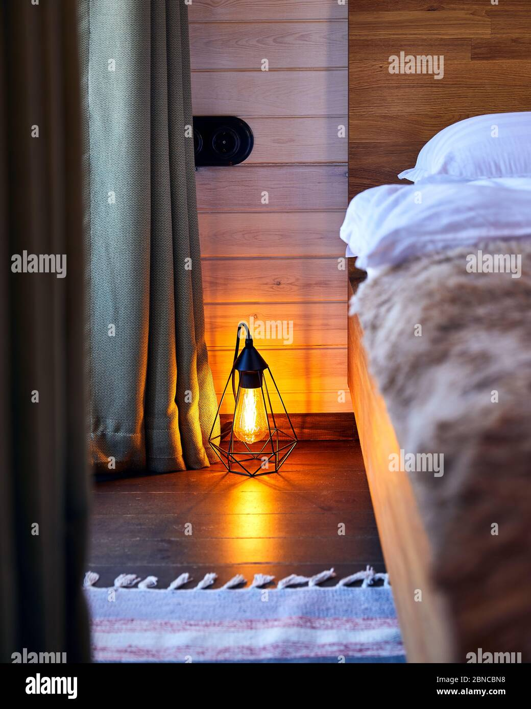 Intérieur moderne de la chambre confortable de l'hôtel avec une lampe de loft illuminée sur le parquet Banque D'Images