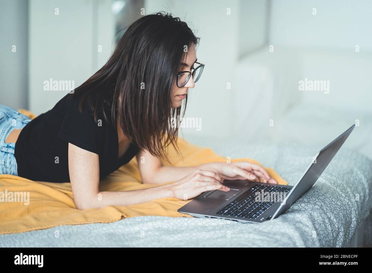 Jolie femme brune portant des lunettes et travaillant sur un ordinateur portable. Femme concentrée couchée au lit à la maison écrivant et utilisant le clavier d'ordinateur portable Banque D'Images