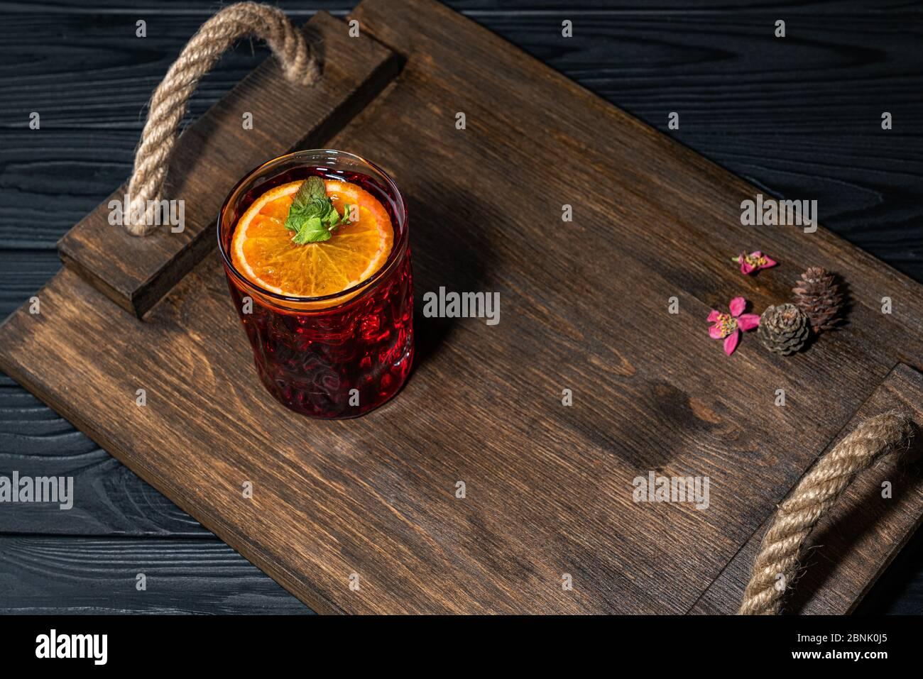 Cocktail traditionnel rouge vif avec whisky sur une planche en bois. Décoration avec des cônes et des petites fleurs roses. Exemple de service parfait Banque D'Images
