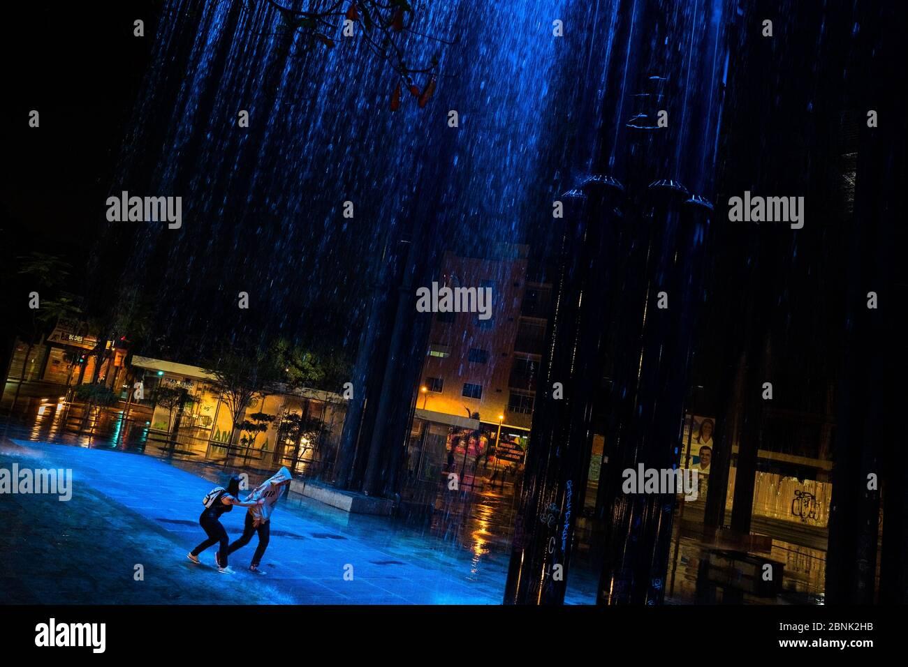 Un jeune couple colombien, se poursuivant, joue autour dans la cascade de rideau de pluie dans le parc Las Chimeneas à Itagüí, Colombie. Banque D'Images