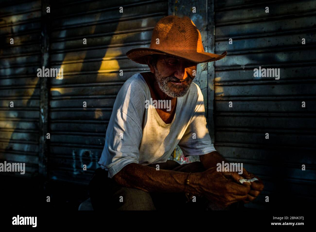 Un vendeur colombien, portant un chapeau de cow-boy, se cache dans l'ombre sur le marché de la Plaza Minorista à Medellín, en Colombie. Banque D'Images