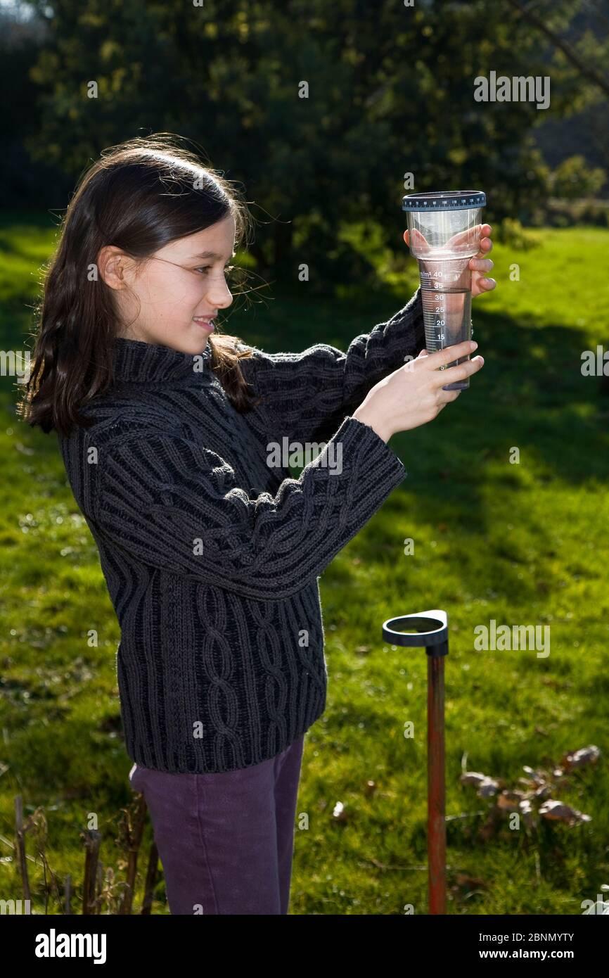 Jeune fille vérifiant un pluviomètre dans un jardin. Bretagne. France. Modèle libéré Banque D'Images