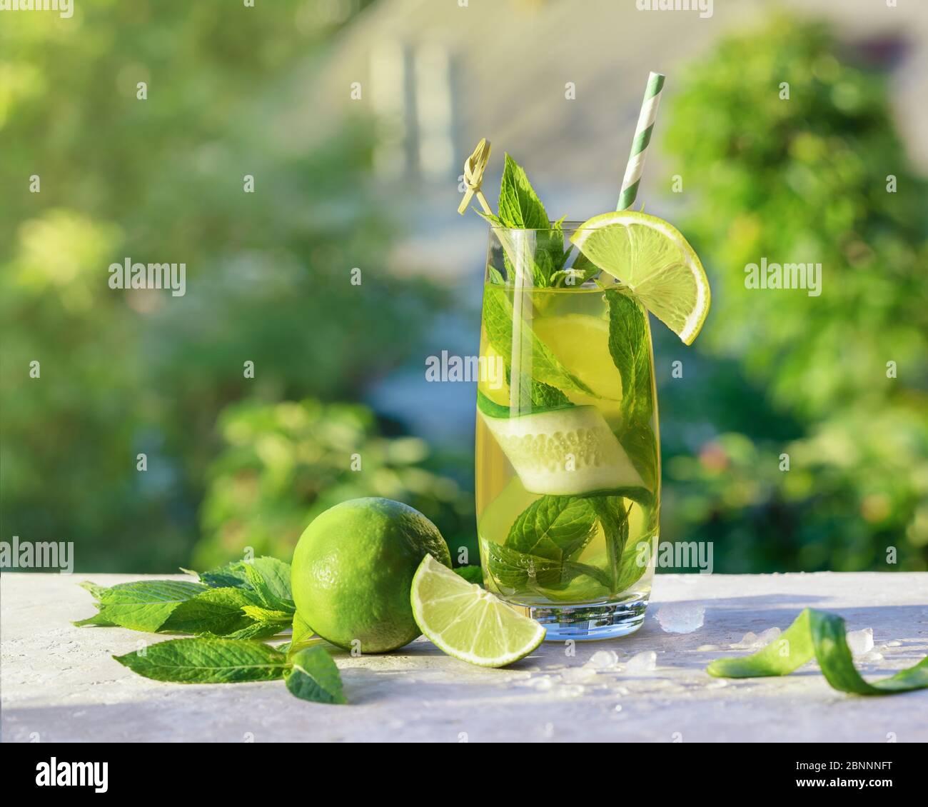 Limonade ou cocktail mojito avec citron vert, concombre et menthe, boisson rafraîchissante froide ou boisson avec glace, extérieur. Eau froide de détox avec du citron et du papier Banque D'Images