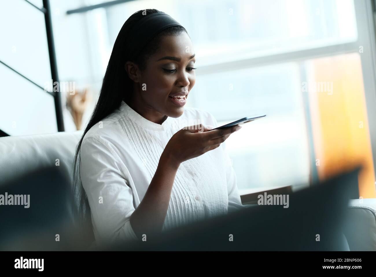 Femme noire utilisant un téléphone portable pour la messagerie vocale Banque D'Images