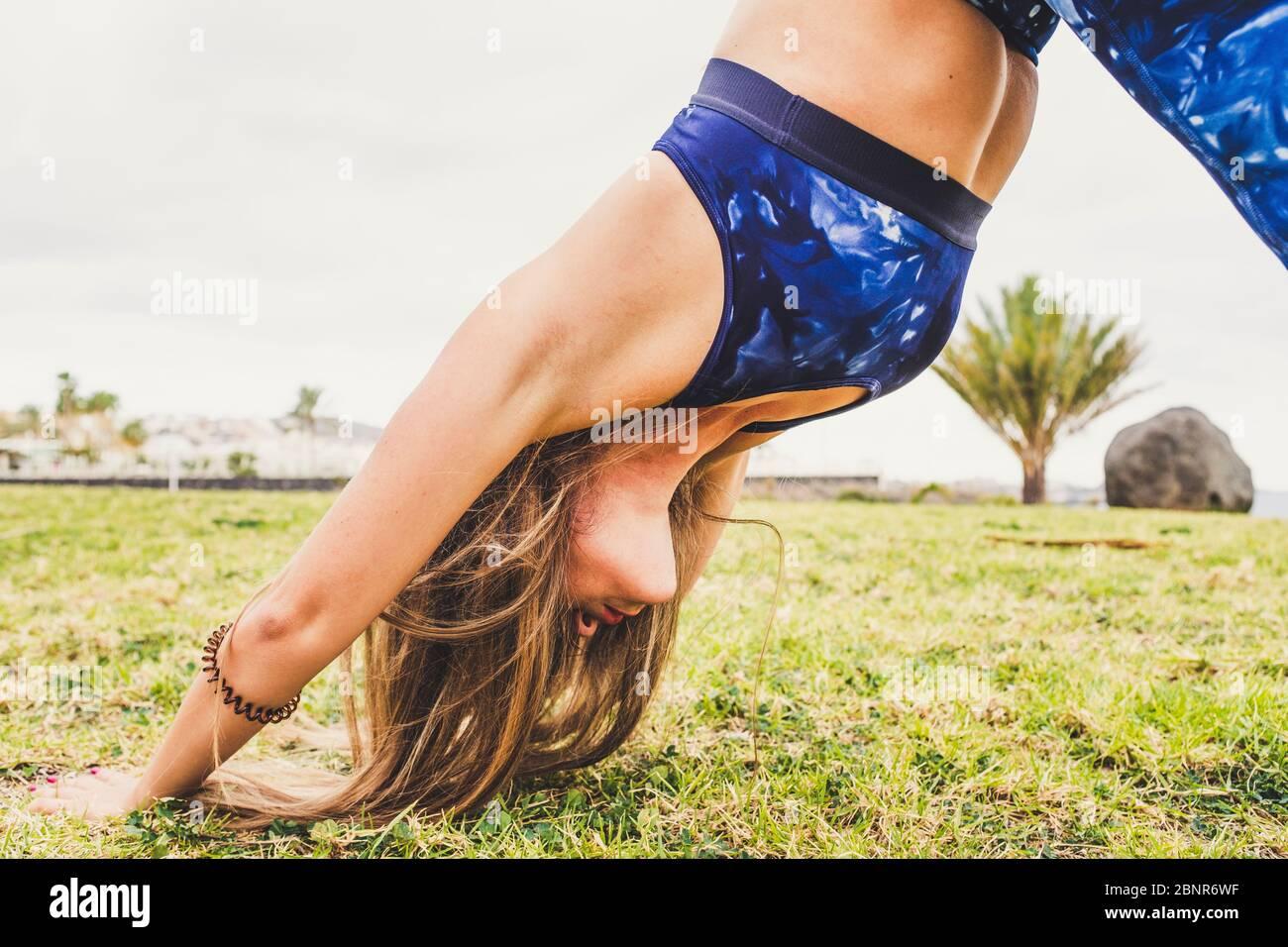 Gros plan de la forme physique saine femme dans le sport Pilates activité au parc sur la nature verte prairie - les gens et l'entraînement outdor - le style de vie actif pour la jeune femme avec les cheveux longs Banque D'Images