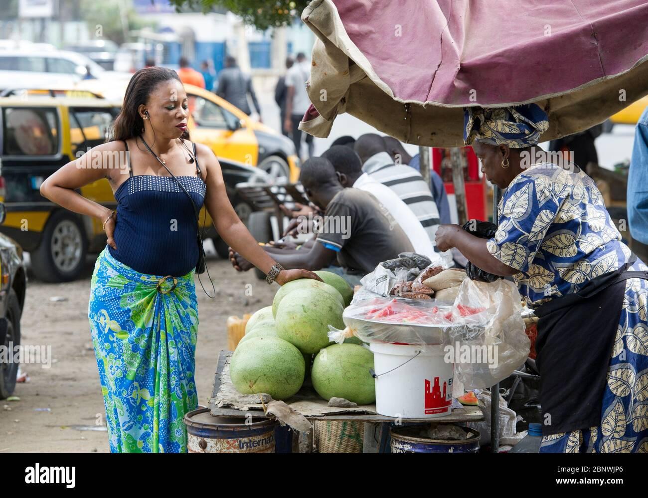 Une femme attend d'être servie sur un marché fruitier à Dakar, Sénégal, Afrique de l'Ouest. Banque D'Images