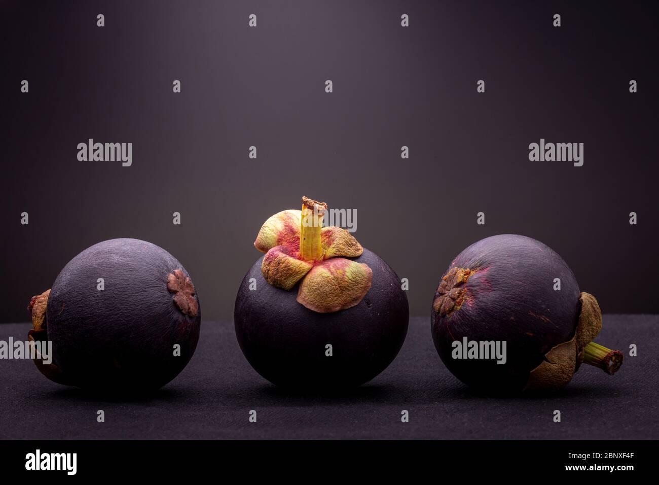 Vous pourrez admirer trois spécimens de fruits mangoustans exotiques rouge-violacé, dont un droit flanqué de deux montrant la partie inférieure. Banque D'Images