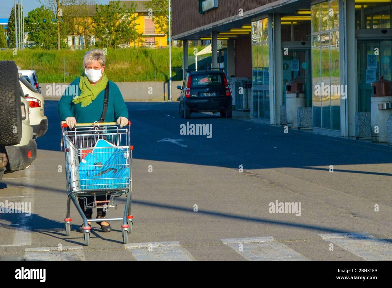 Vieille femme italienne, pensionnée portant un masque facial coronavirus poussant son panier à l'extérieur d'une épicerie. Lady craint pour la pandémie de COVID-19. Banque D'Images