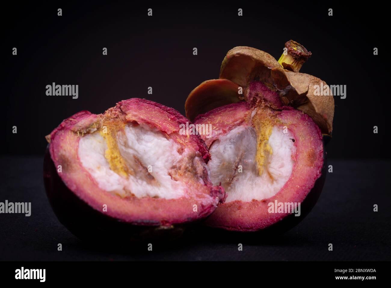 Deux moitiés d'un fruit de mangoustan exotique rouge-violacé montrant la pulpe blanche intérieure et la couche épaisse de peeling rouge avec le dessus encore. Banque D'Images