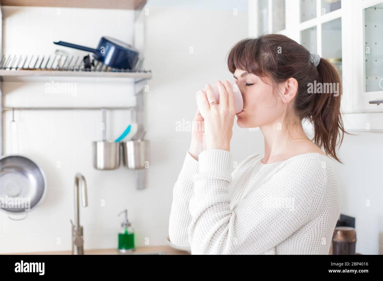 Jolie femme caucasienne, avec des lanières et de la queue de cheval, buvant une tasse de café le matin dans une cuisine blanche et lumineuse. Portrait de profil, yeux proches Banque D'Images