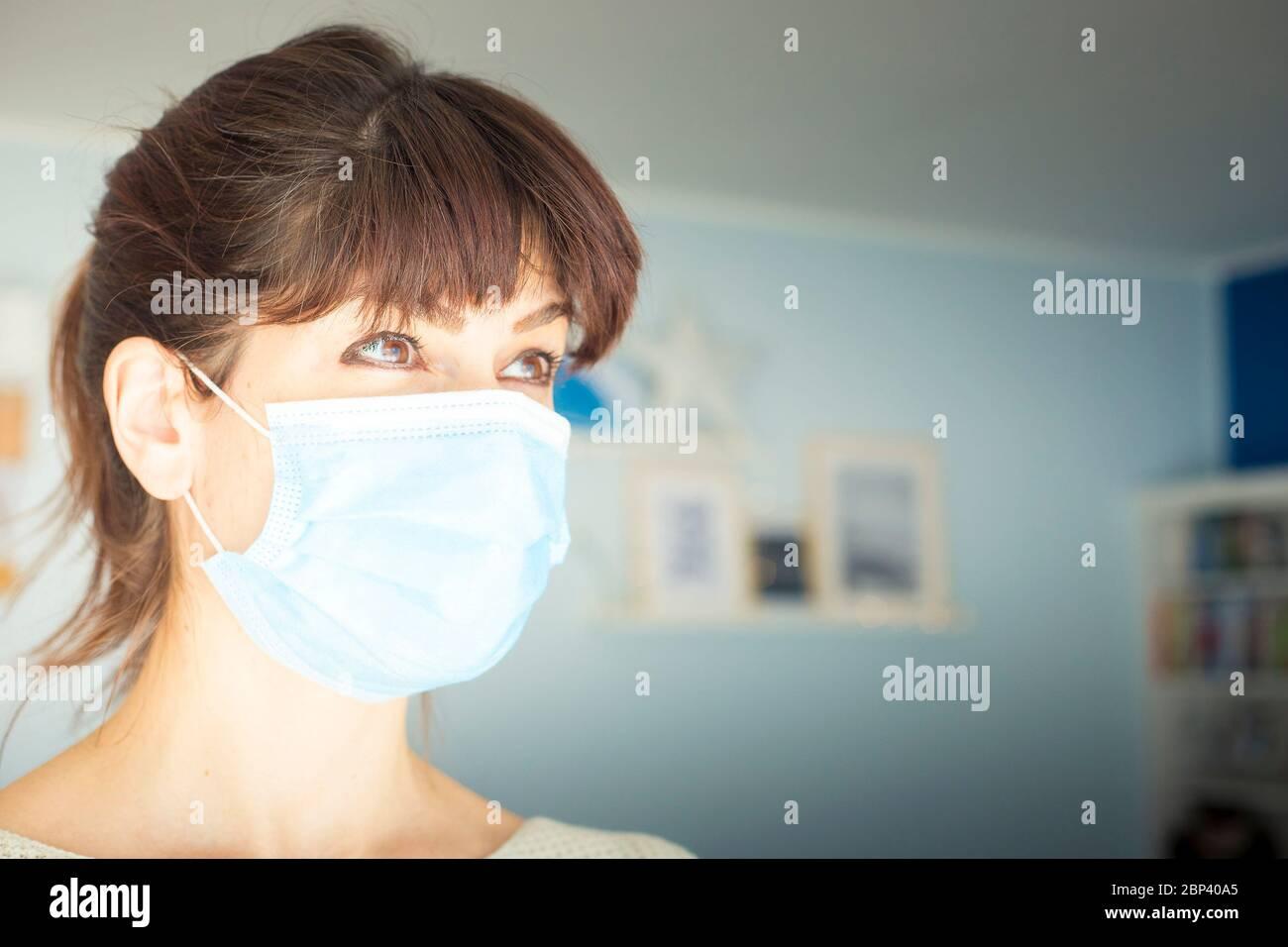 Femme caucasienne attirante avec de longs cheveux et des langes, portant un masque chirurgical bleu pendant une pandémie de covid-19 ou de coronavirus. En regardant loin, l'espace de copie Banque D'Images