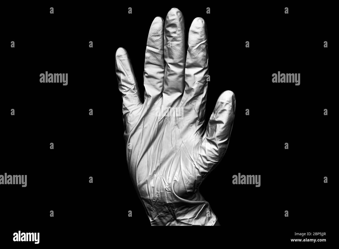 Main humaine dans un gant médical en caoutchouc blanc sur fond noir isolé de près, une main chirurgien dans un gant de protection en latex, main médecin dans un gant Banque D'Images
