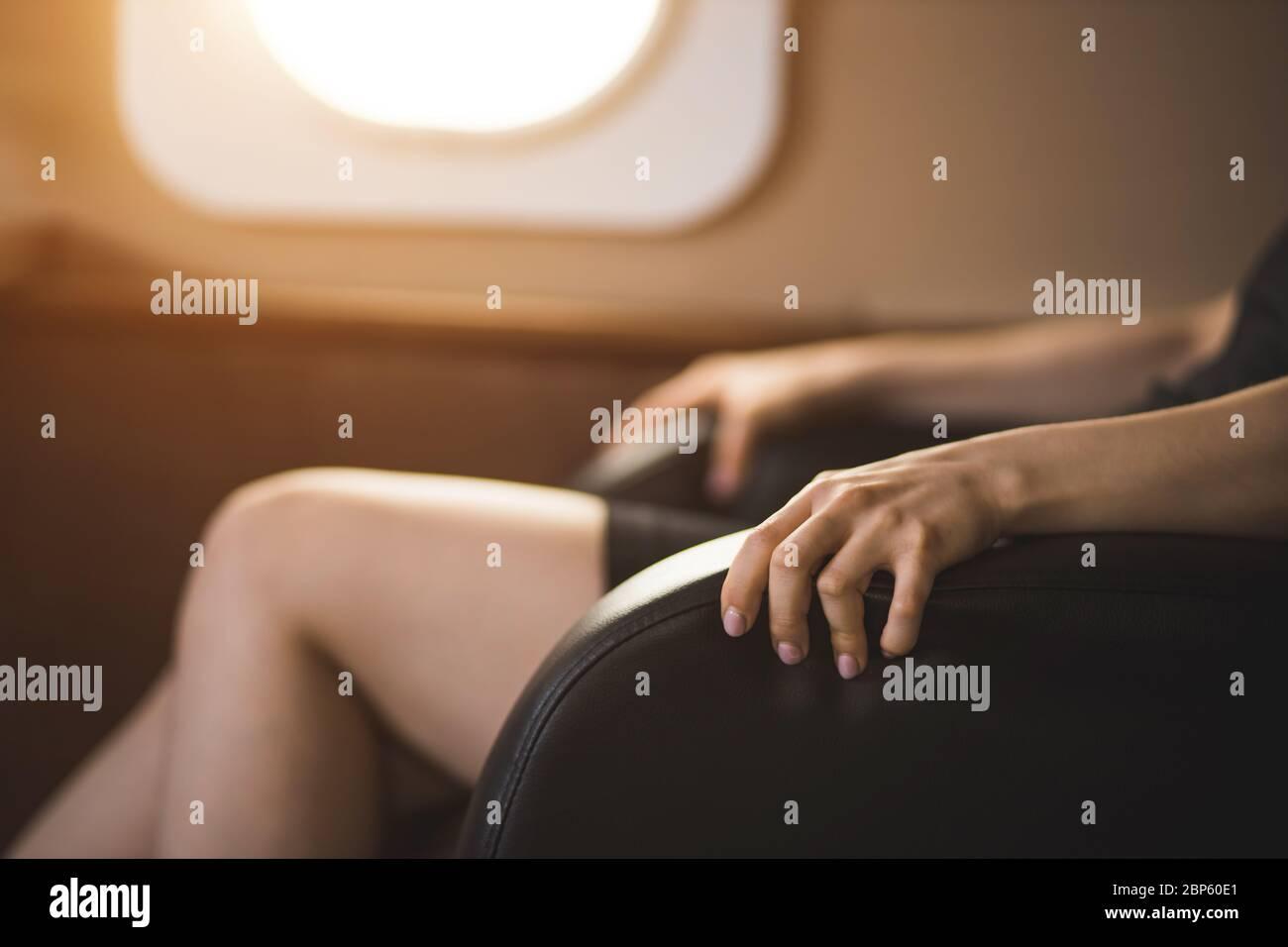 Photo courte d'une femme d'affaires avec peur de vol dans un jet privé. Foyer sélectif de la femme terrifiée assis encombrer les bras de la chaise en privé p Banque D'Images