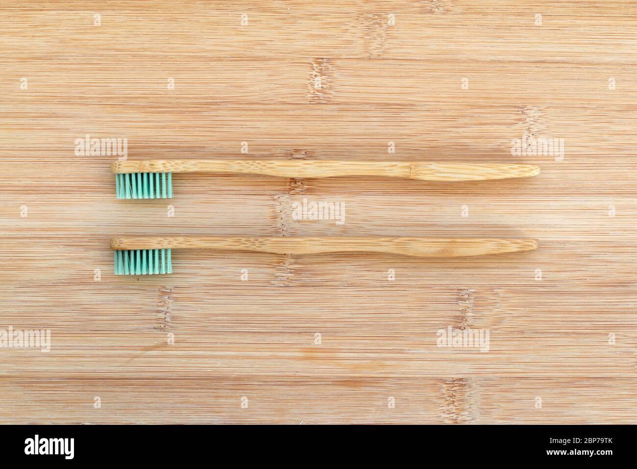 Ensemble de deux brosses à dents en bambou sur fond de bois. Zéro déchet, matériau biodégradable, concept d'environnement Banque D'Images
