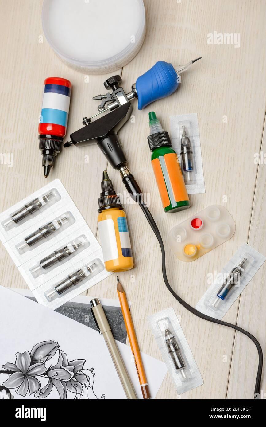 Machine à tatouer, pigments, aiguilles, stylos sur bureau en bois blanc Banque D'Images