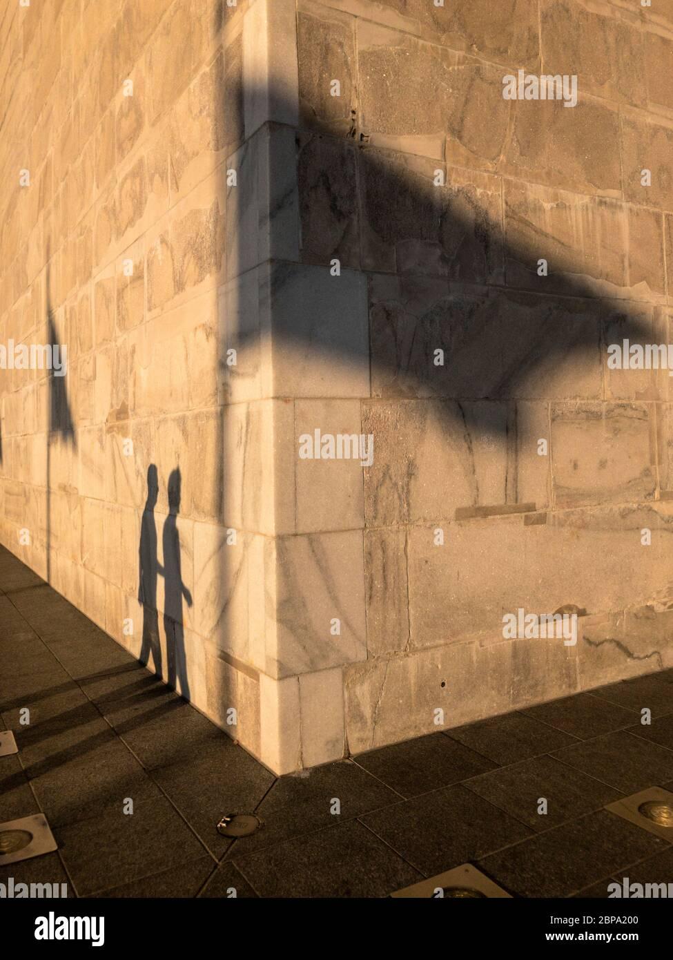 Ombre des visiteurs et drapeaux ondulant coulés sur la base du Washington Monument au coucher du soleil, Washington, D.C., États-Unis Banque D'Images